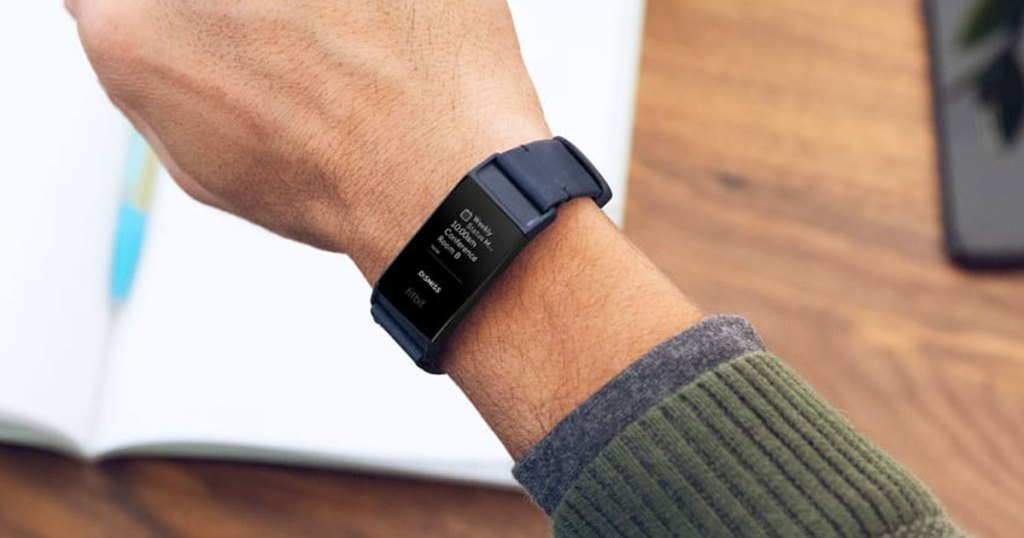 man wearing a green sweater with a black fitbit charge on his wrist