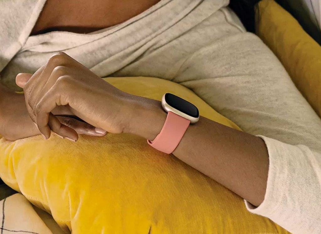 woman in a light grey sweater holding up her wrist to check a pink and gold fitbit