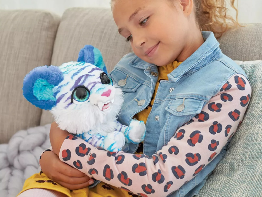 little girl holding an interactive furreal kitty