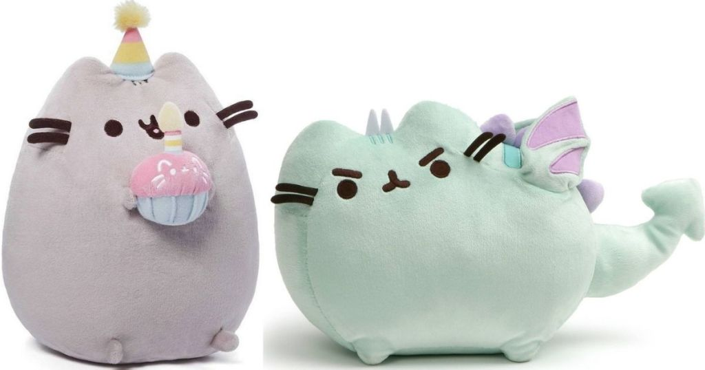 two plush cats one holding a cupcake and one with wings