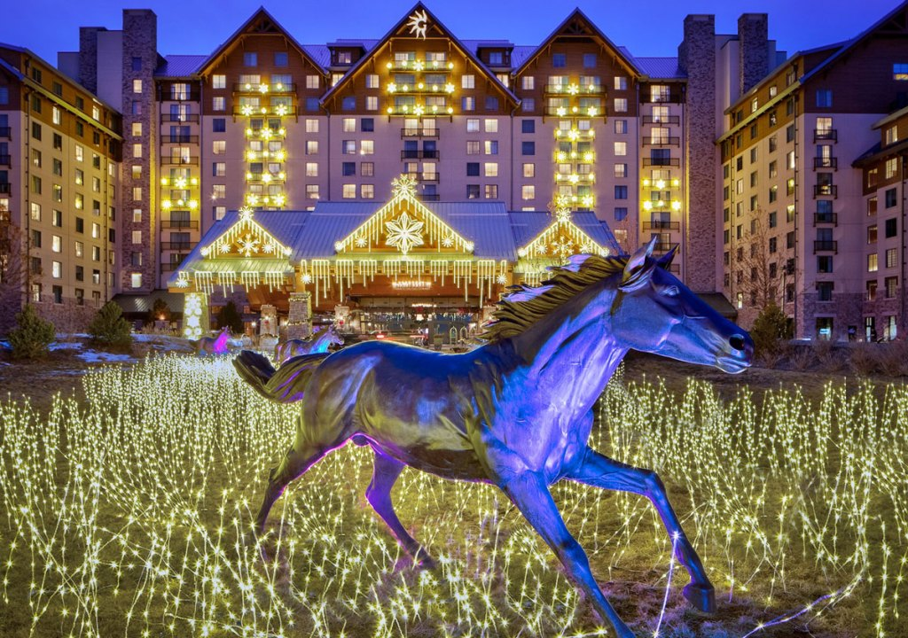 Gaylord Rockies hotel covered in white christmas lights with statue of horse in front of building