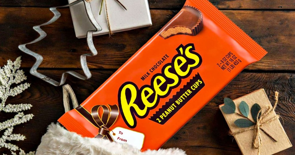 giant reese's peanut butter cups package sticking out of a stocking on a wood table