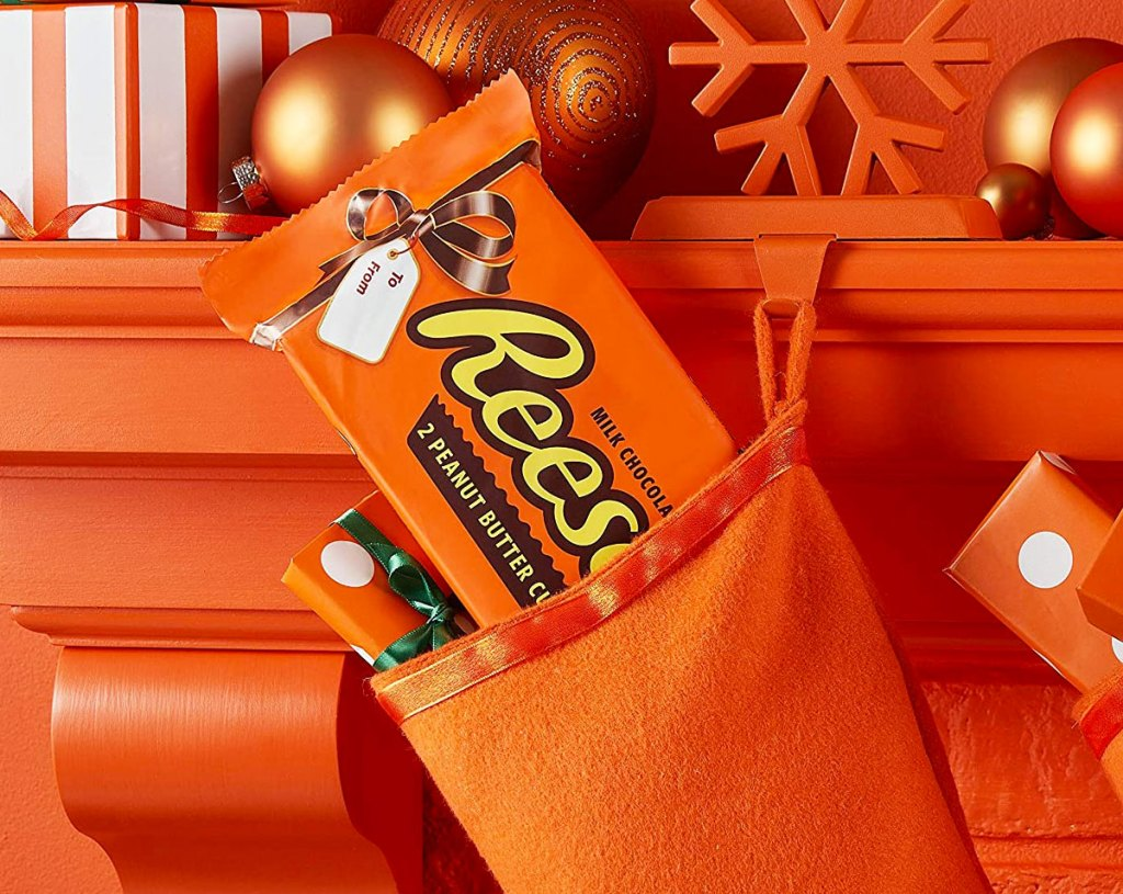giant reese's peanut butter cup package sticking out of an orange stocking