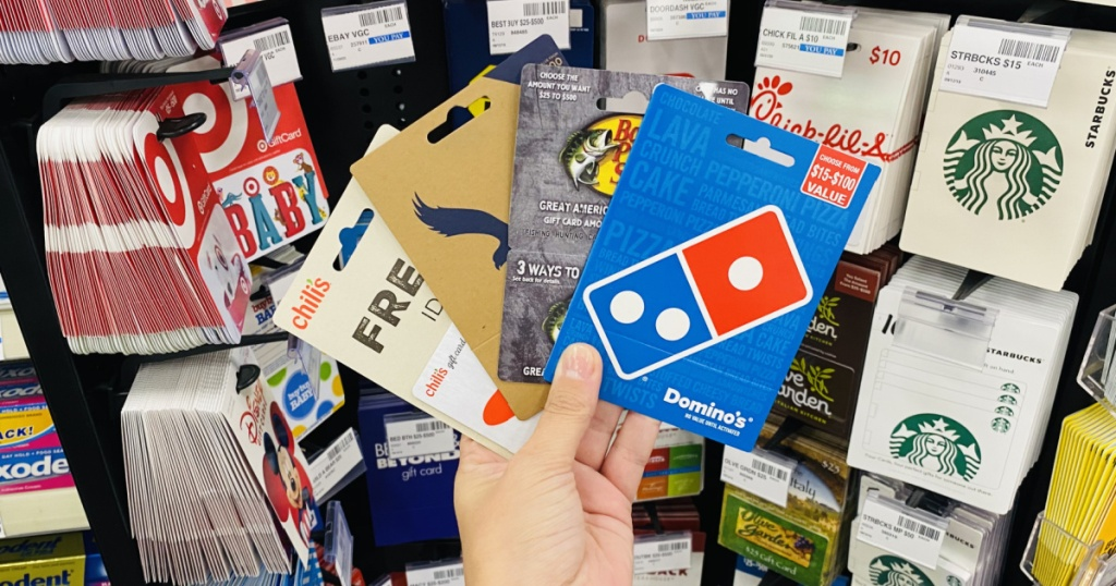 hand holding gift cards in front of gift card display in store