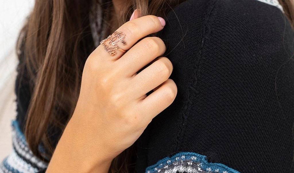 womans hand with a ring on it that has three names