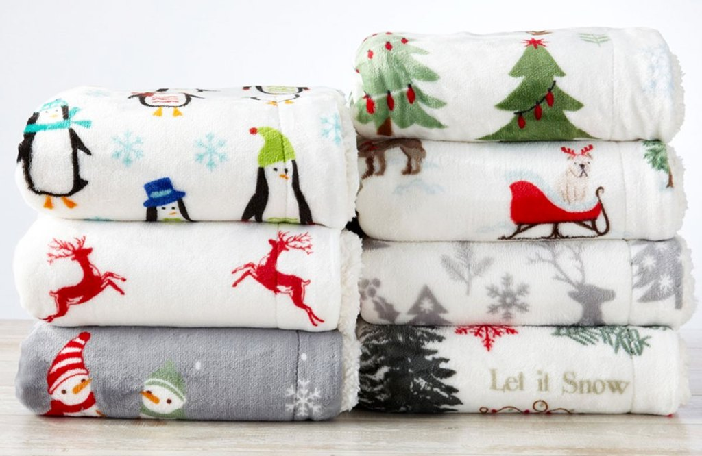 two stacks of christmas printed throw blankets