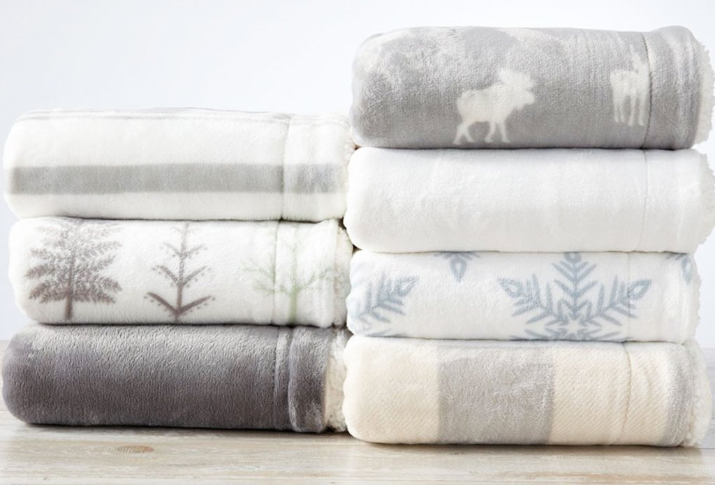 two stacks of folded throw blankets in grey and white themed prints