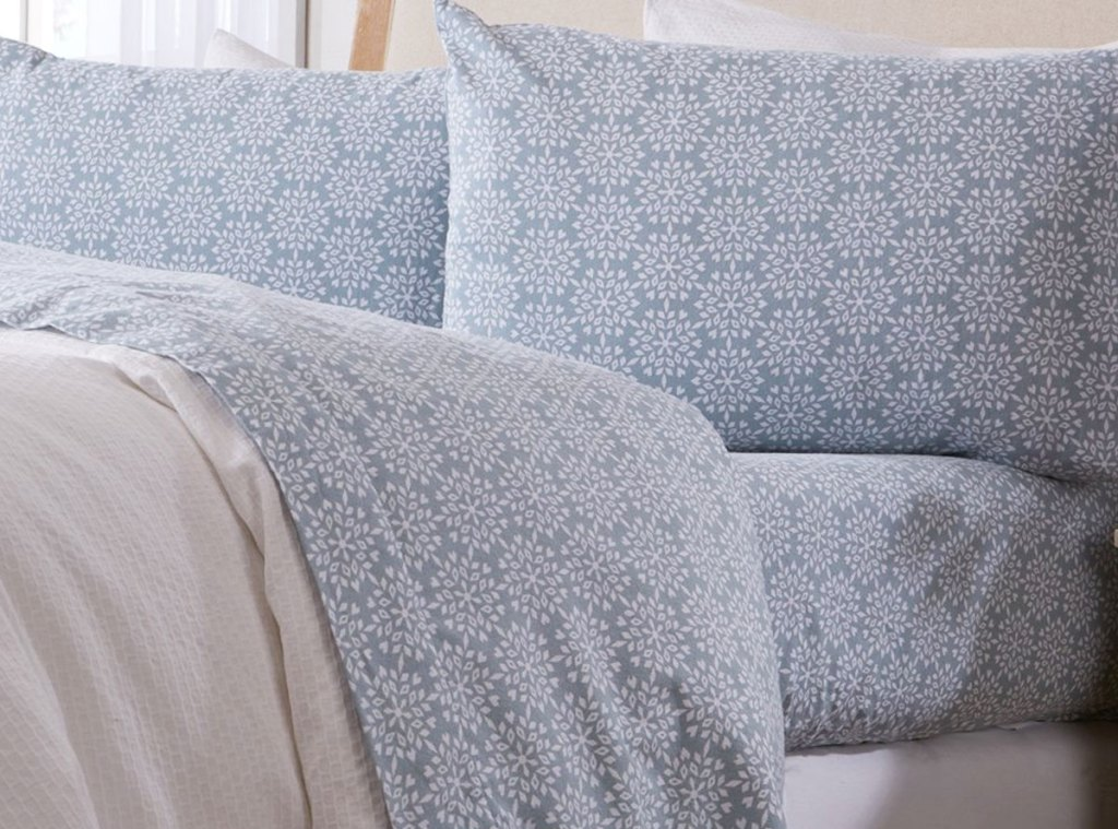 bed made with light blue flannel sheet set with white snowflake print