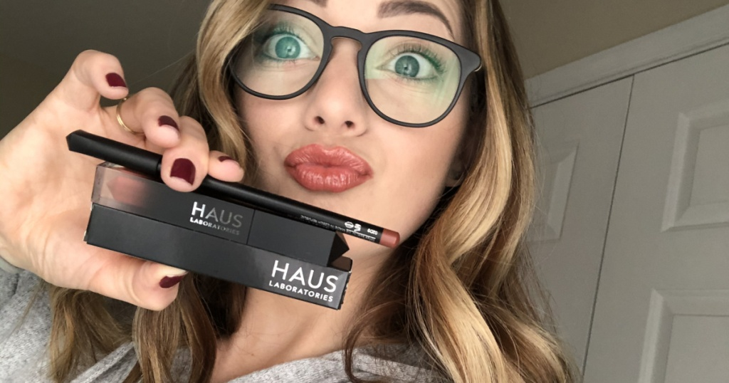 HAUS ladoratories lip kit in womans hand near face