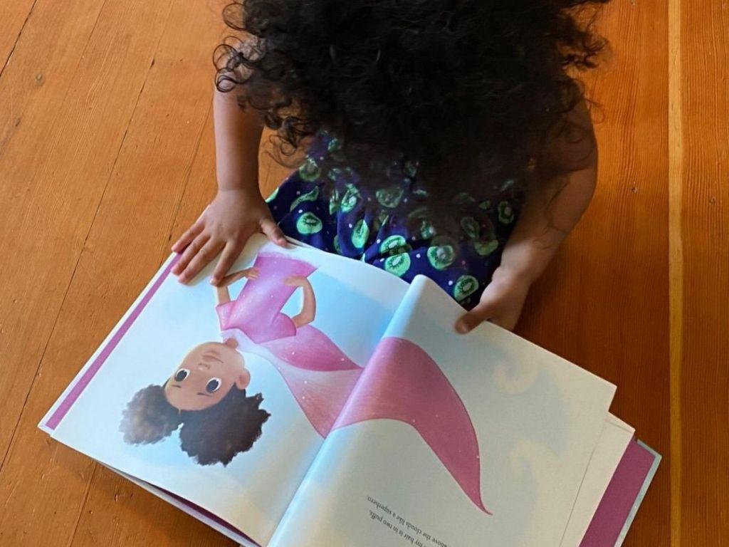 Little Girl reading Hair Love book