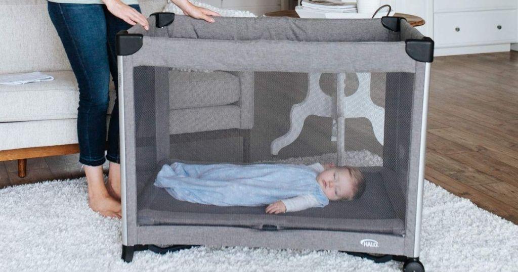 baby sleeping in a portable crib