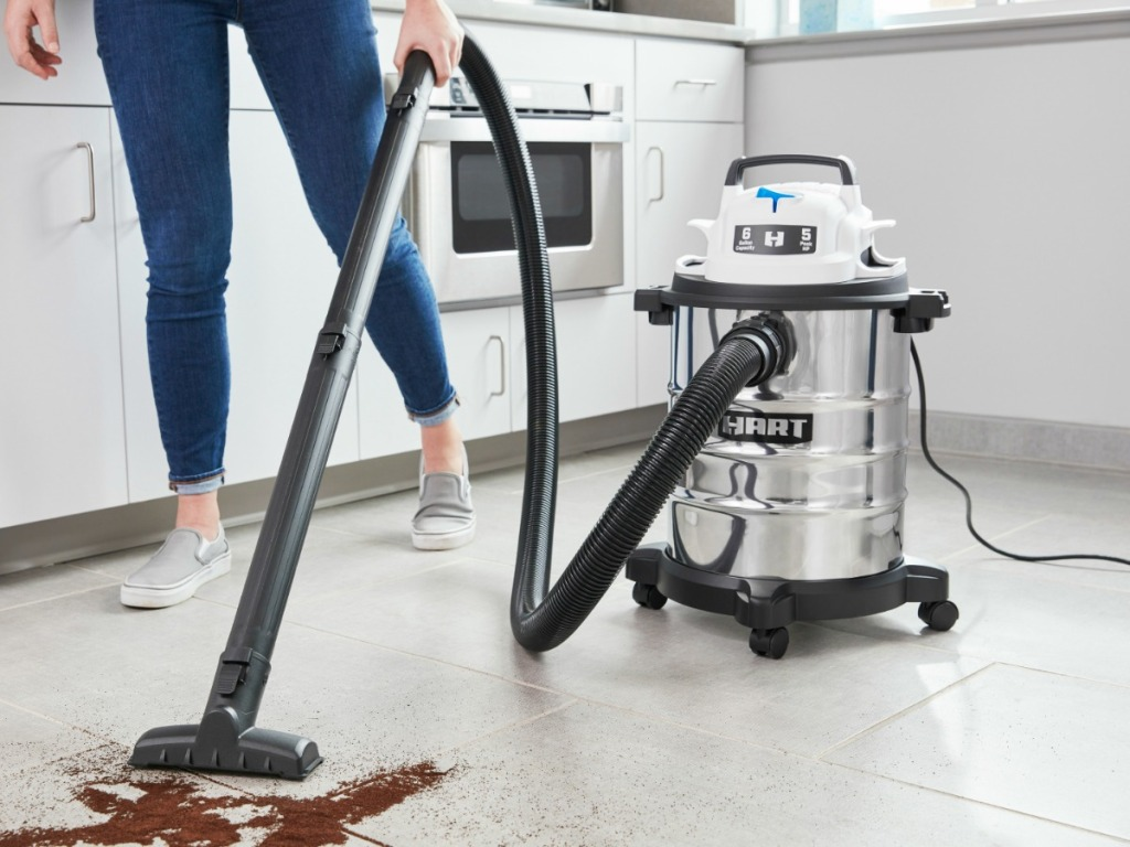 Hart brand wet/dry vacuum cleaner being used to clean up dirt on kitchen floor