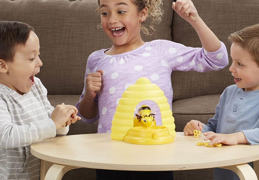 three kids sitting at table playing with beehive game
