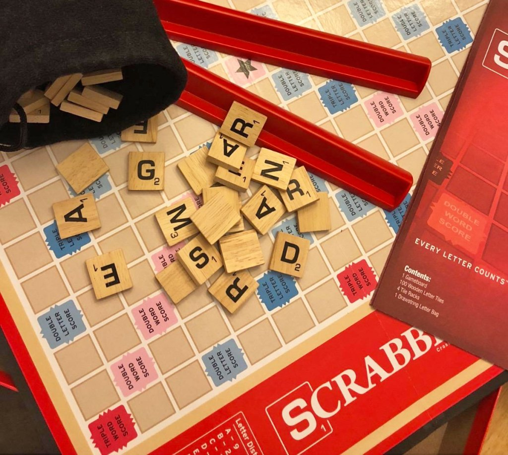 scrabble board game with letters and tile holders on top of board