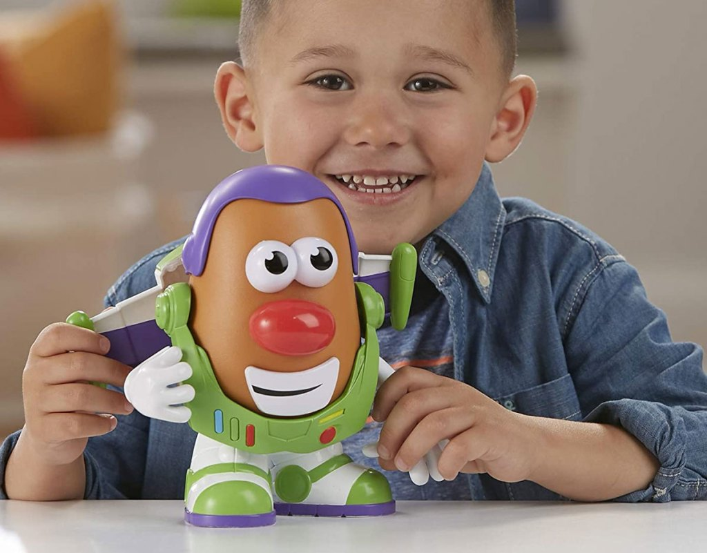 toddler boy smiling holding a buzz lightyear themed mr potato head toy