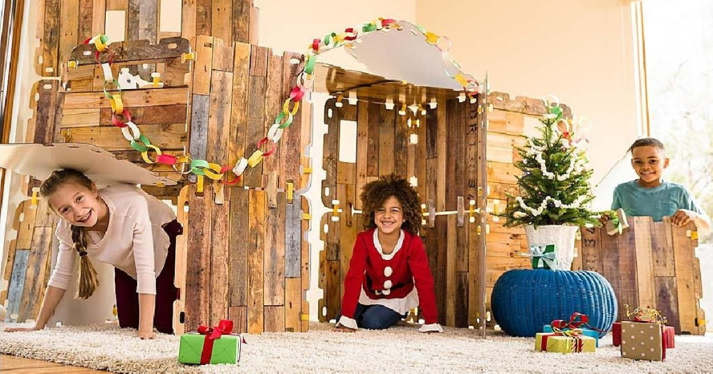three kids playing with buildable fort in living room with Christmas presents and decor