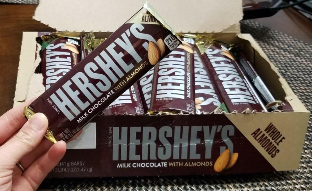 hand holding chocolate almond bar and box of chocolate almond bars on table