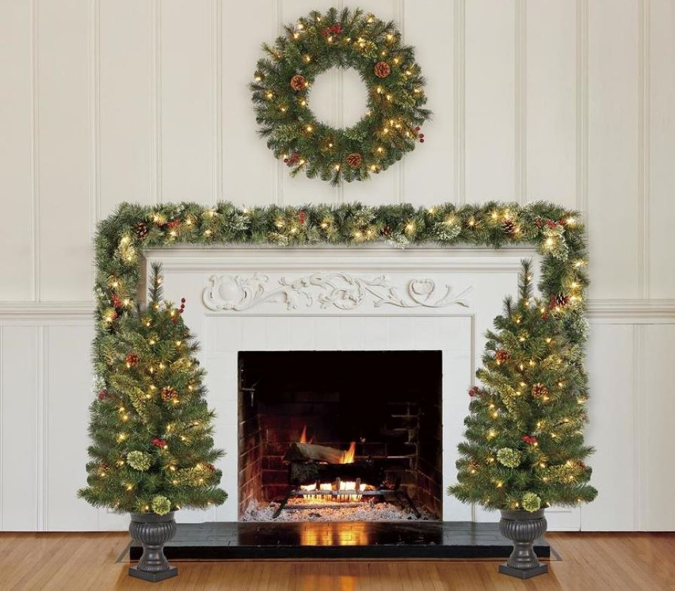 wreath, garland and trees by a fireplace