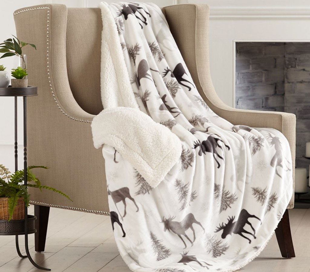 white moose printed sherpa throw blanket draped over an accent chair