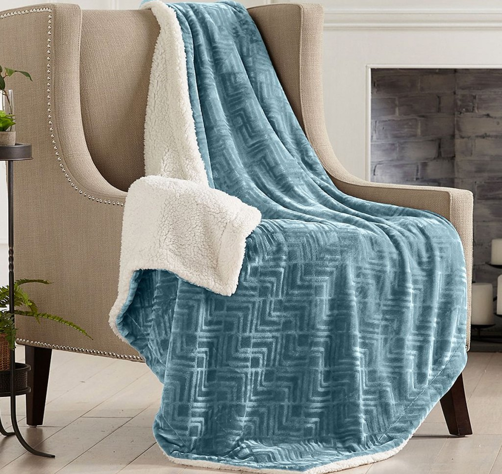 blue textured throw with white sherpa lining draped over an accent chair