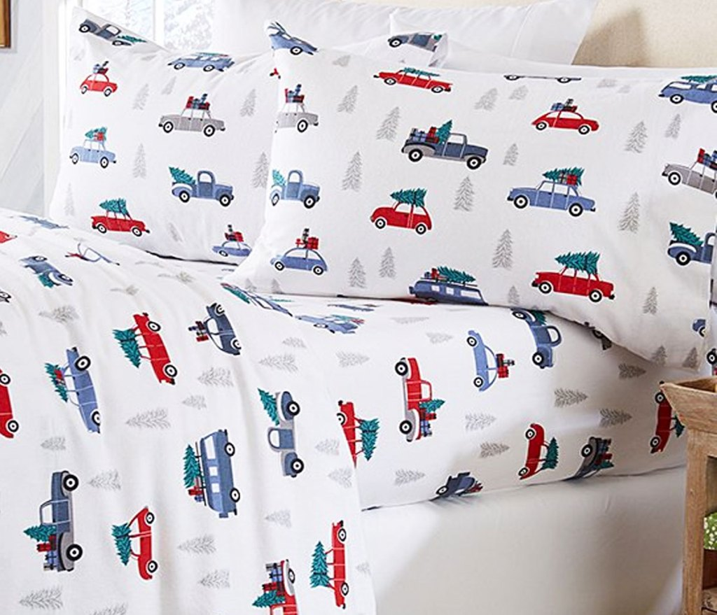 bed with white flannel sheet set with blue and red cars with christmas trees on top of them