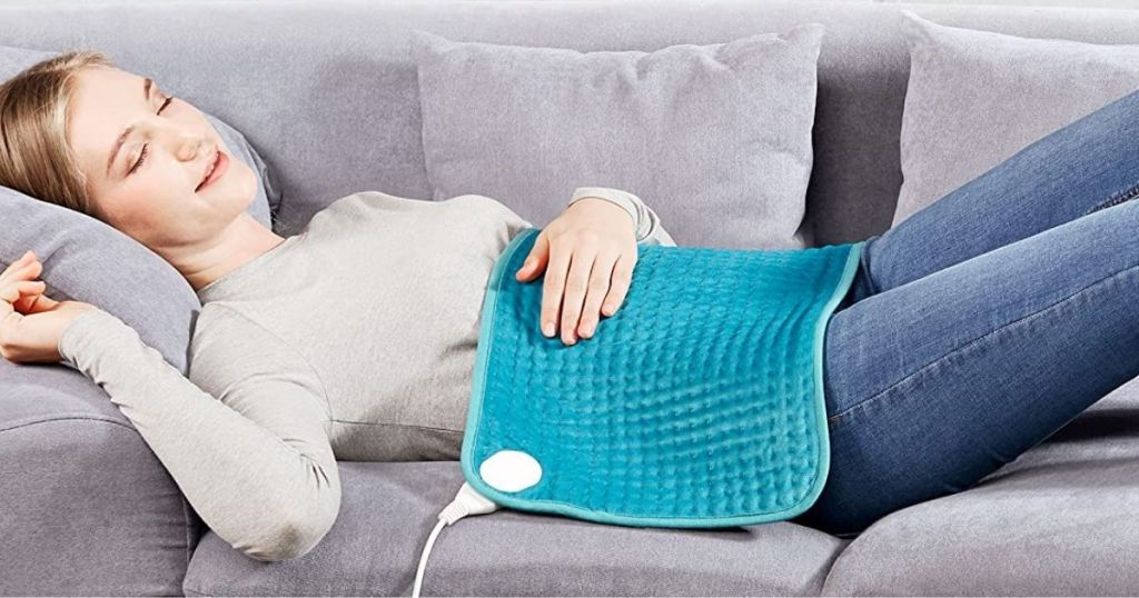 woman laying on a couch with a heating pad