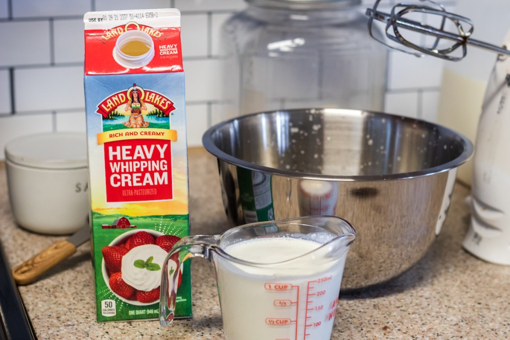 stainless steel bowl with heavy cream and measuring tools
