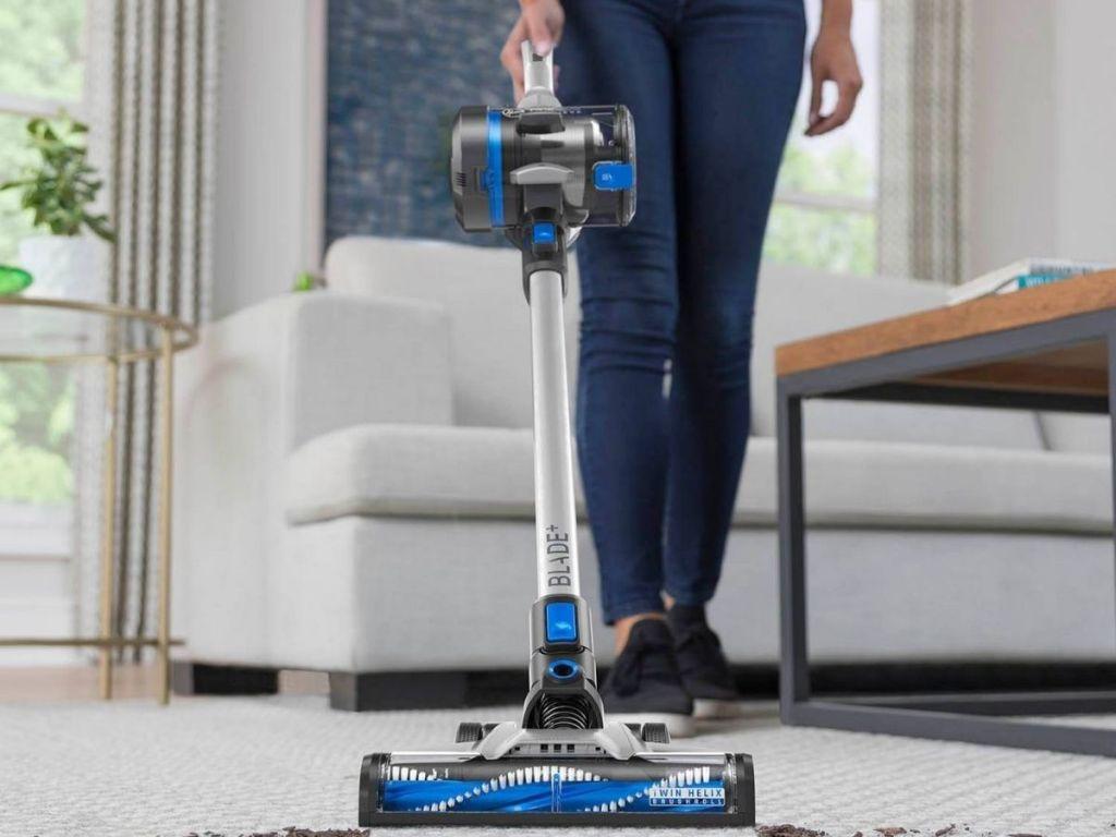 woman using stick vacuum