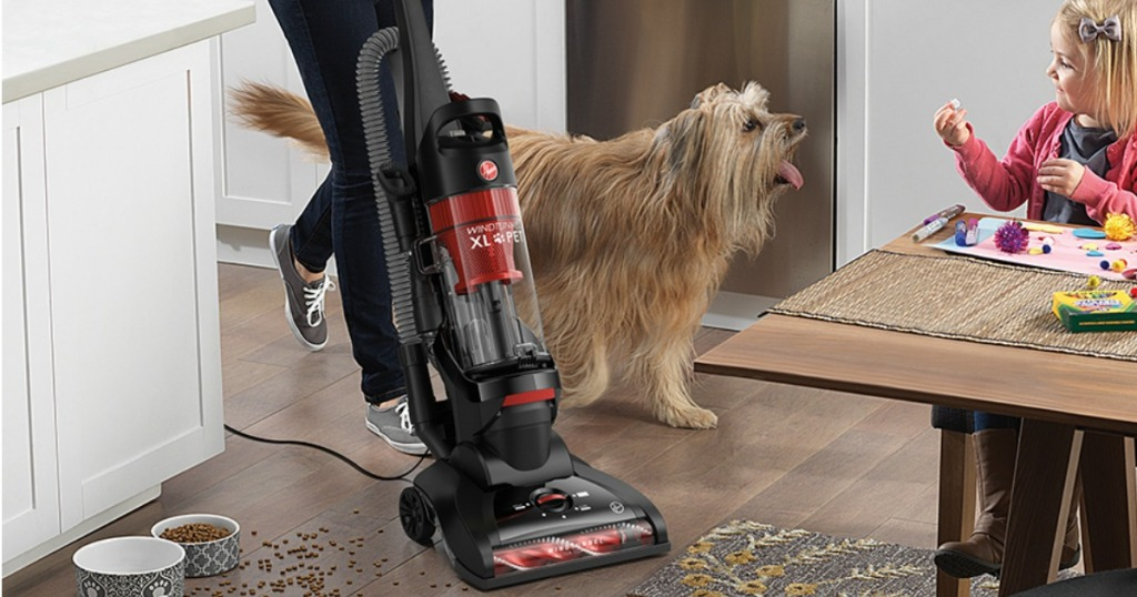 Woman using an upright vacuum in the kitchen near a dog