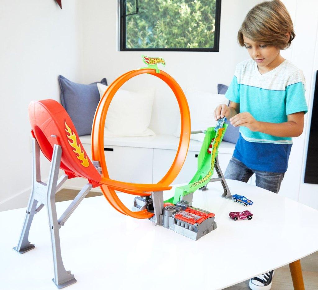 anak laki-laki dengan kaos biru dan putih bermain dengan trek lingkaran roda panas di atas meja putih