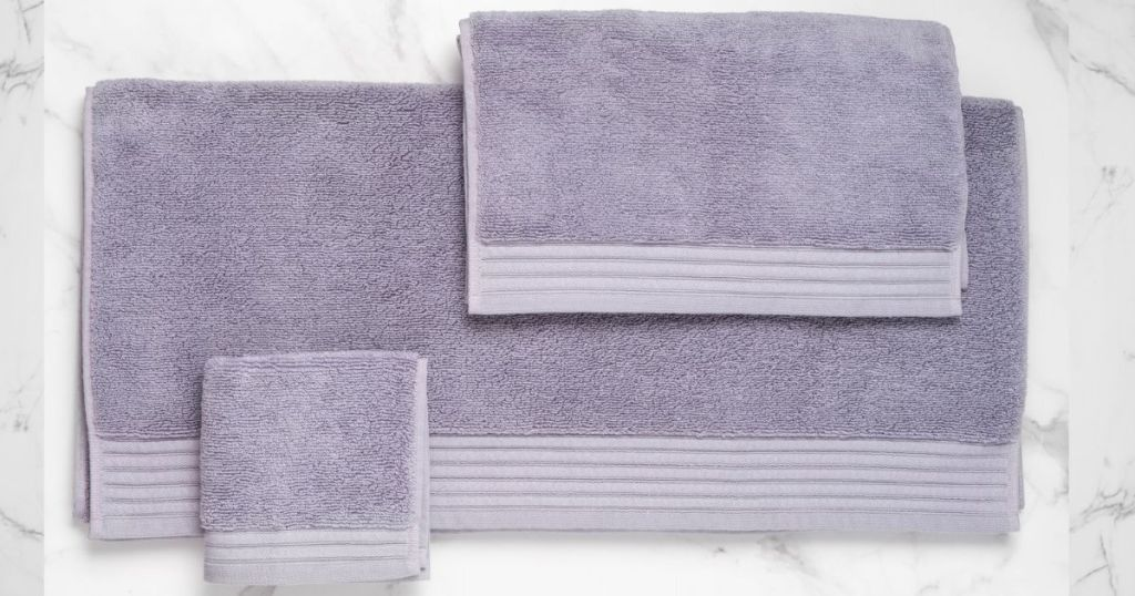 purple hand towel and wash cloths resting on white and gray marble surface