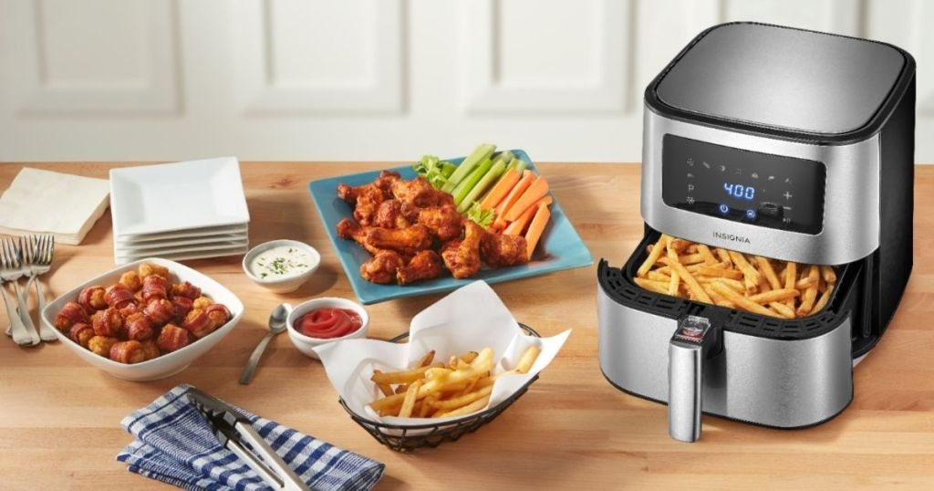 insignia stainless steel air fryer on counter with basket filled with fries