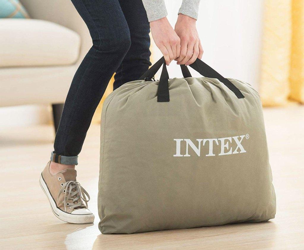 wanita mengambil tas penyimpanan merek intex dari lantai kayu