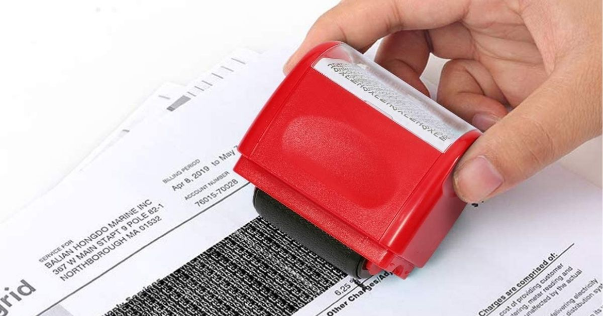 hand using red stamp to black out personal information on document