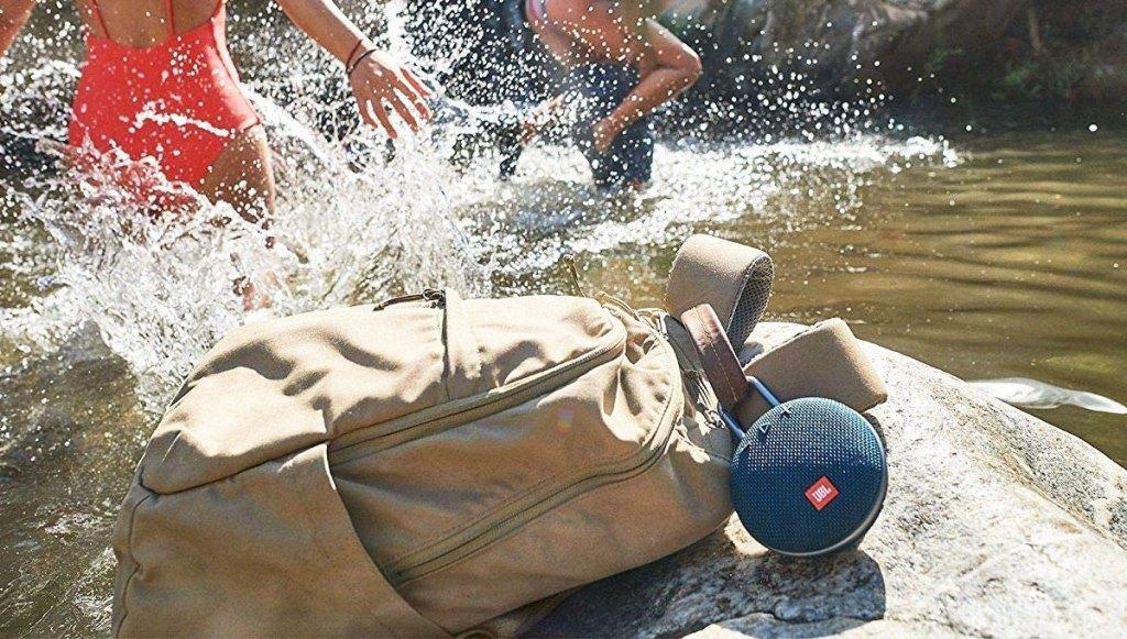 round JBL speaker clipped onto backpack near river edge