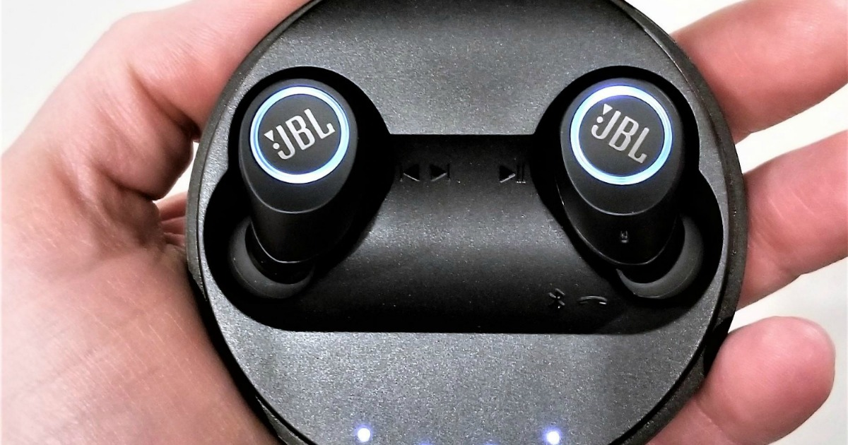 hand holding a pair of in-ear jbl wireless earbuds in charging case
