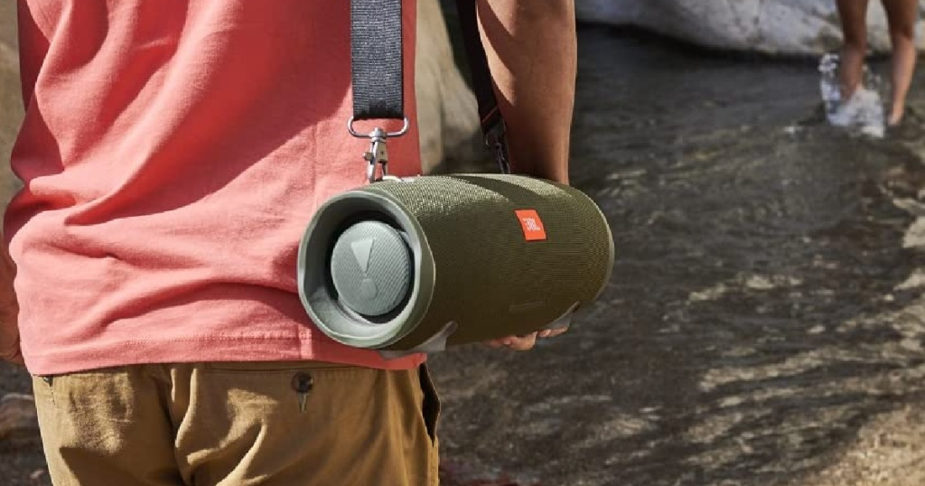 man walking outdoors and carrying green speaker