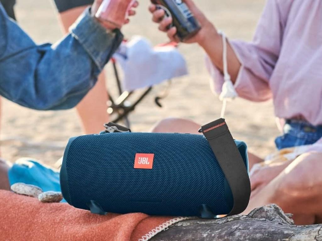 orang dengan minuman dan pembicara biru di pantai