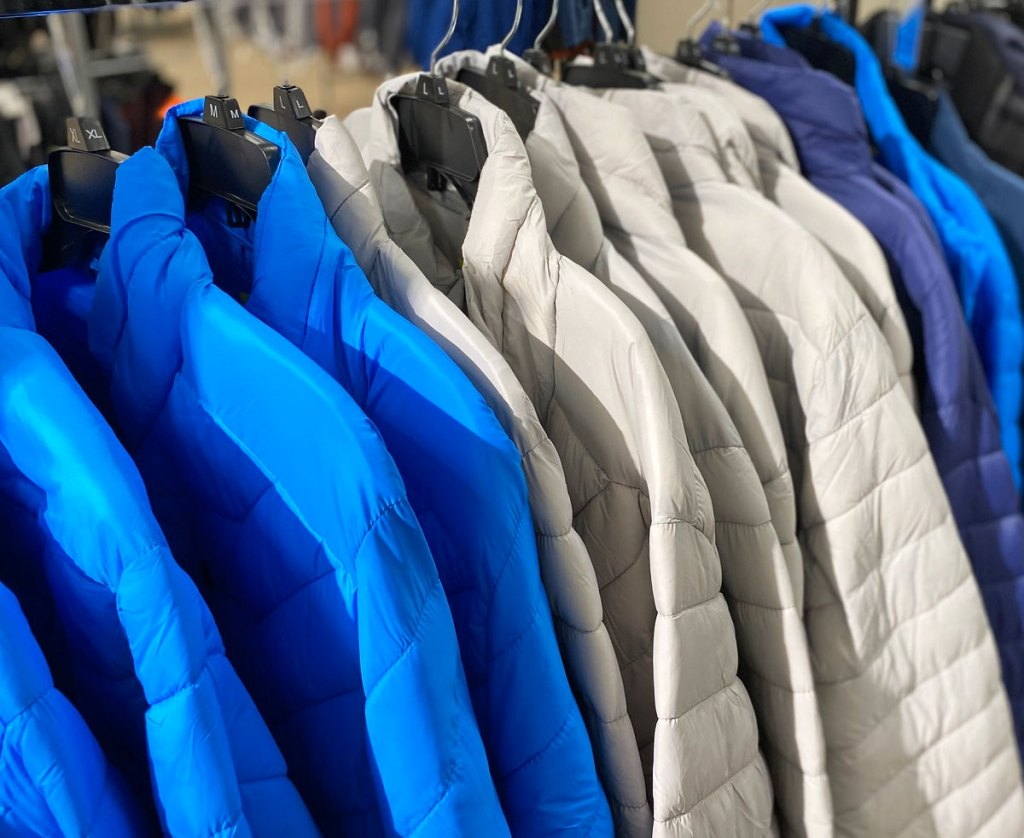 bright blue and light grey puffer jackets on hangers