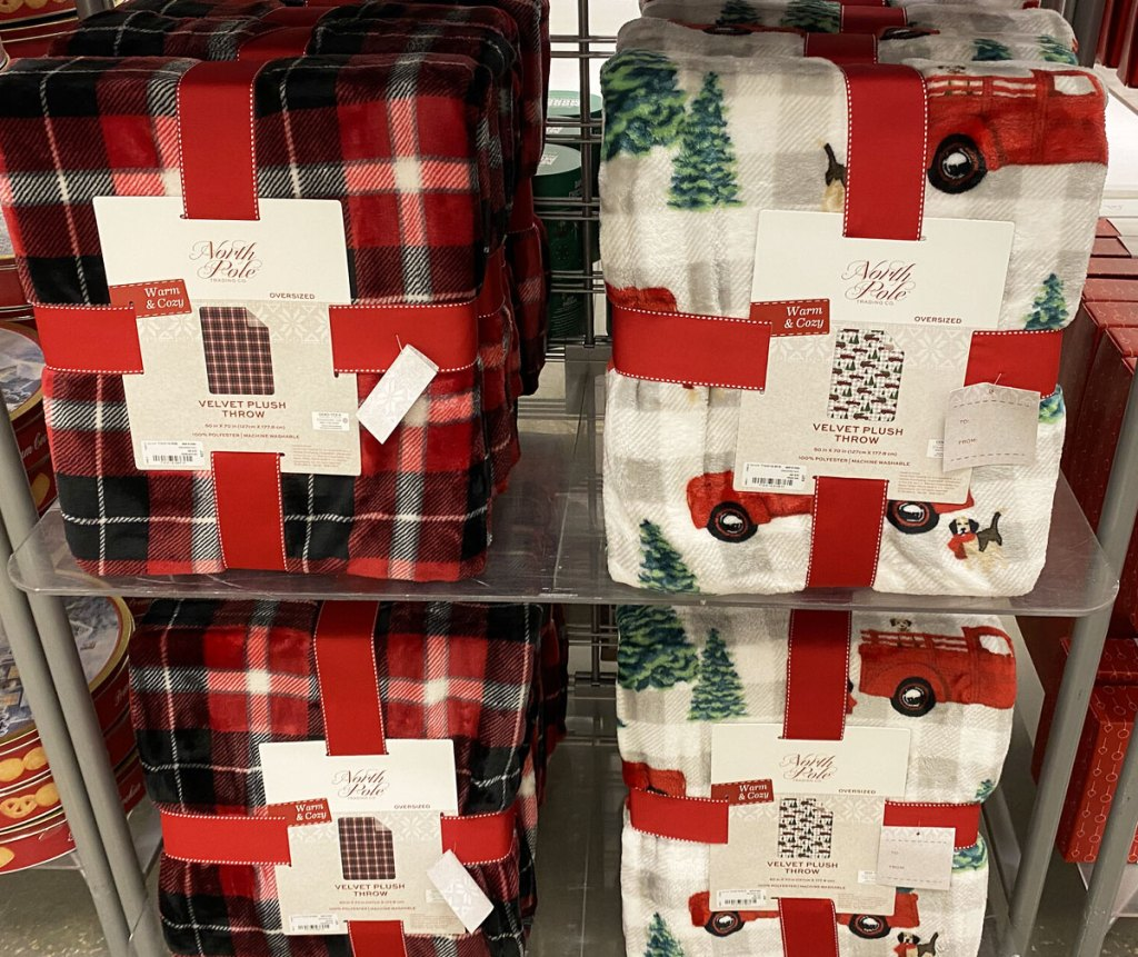 red and black plaid and red car with christmas tree print throw blankets on display at JCPenney