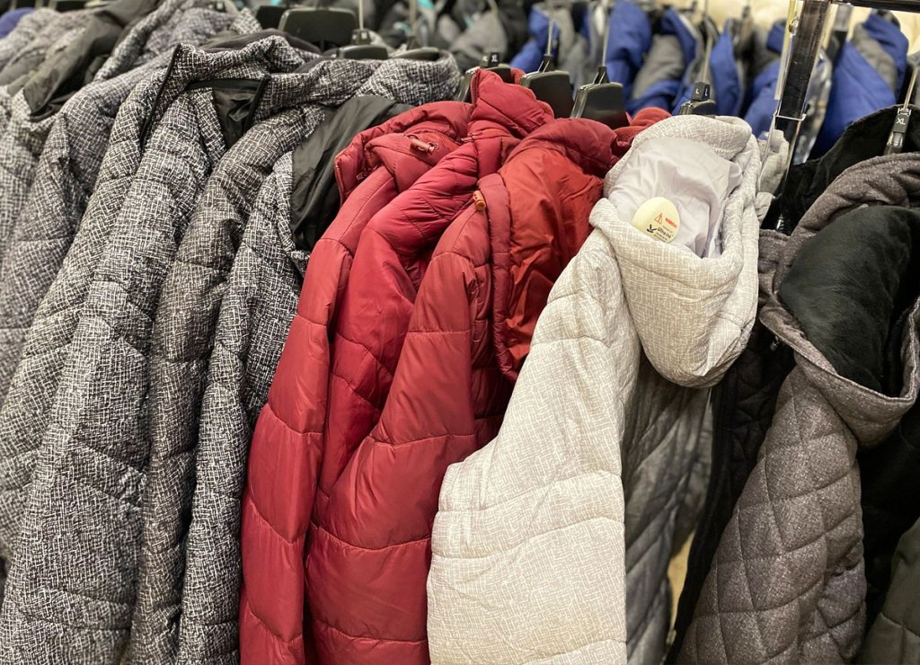 grey, maroon, and white colored puffer jackets on hangers