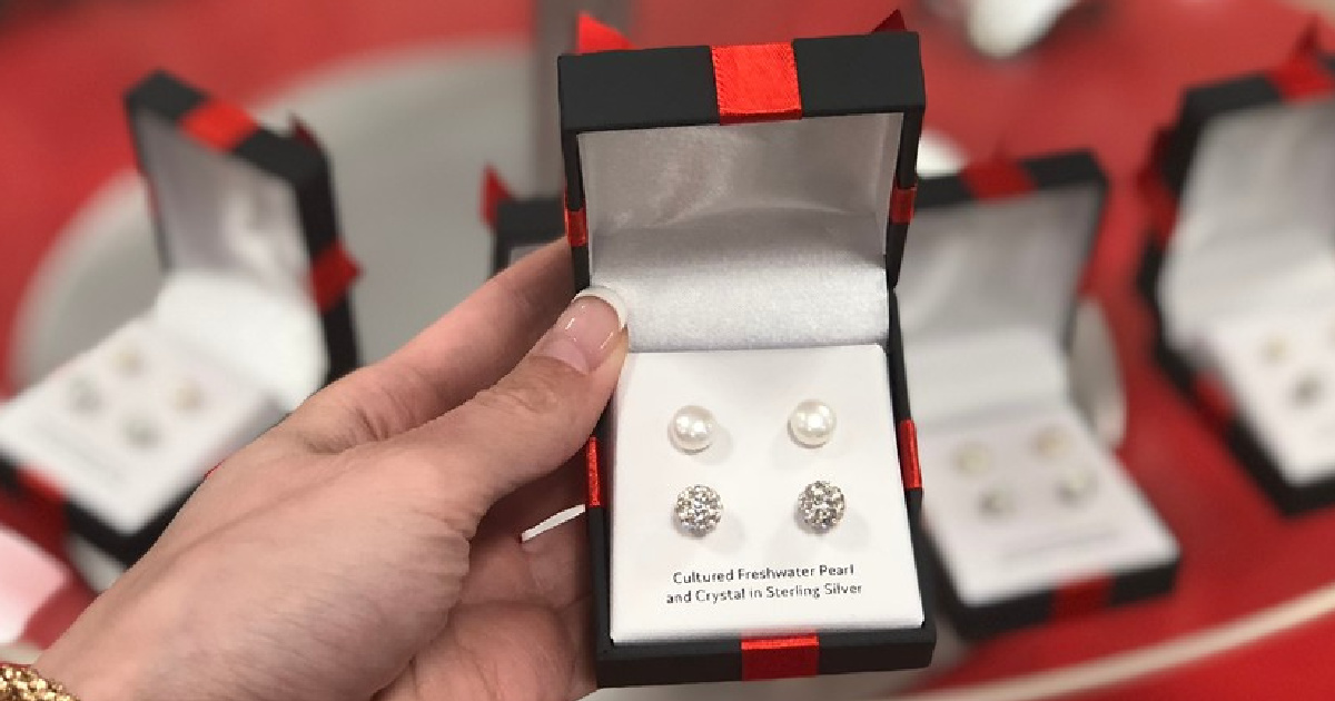 hand holding gift box with two pairs of earrings