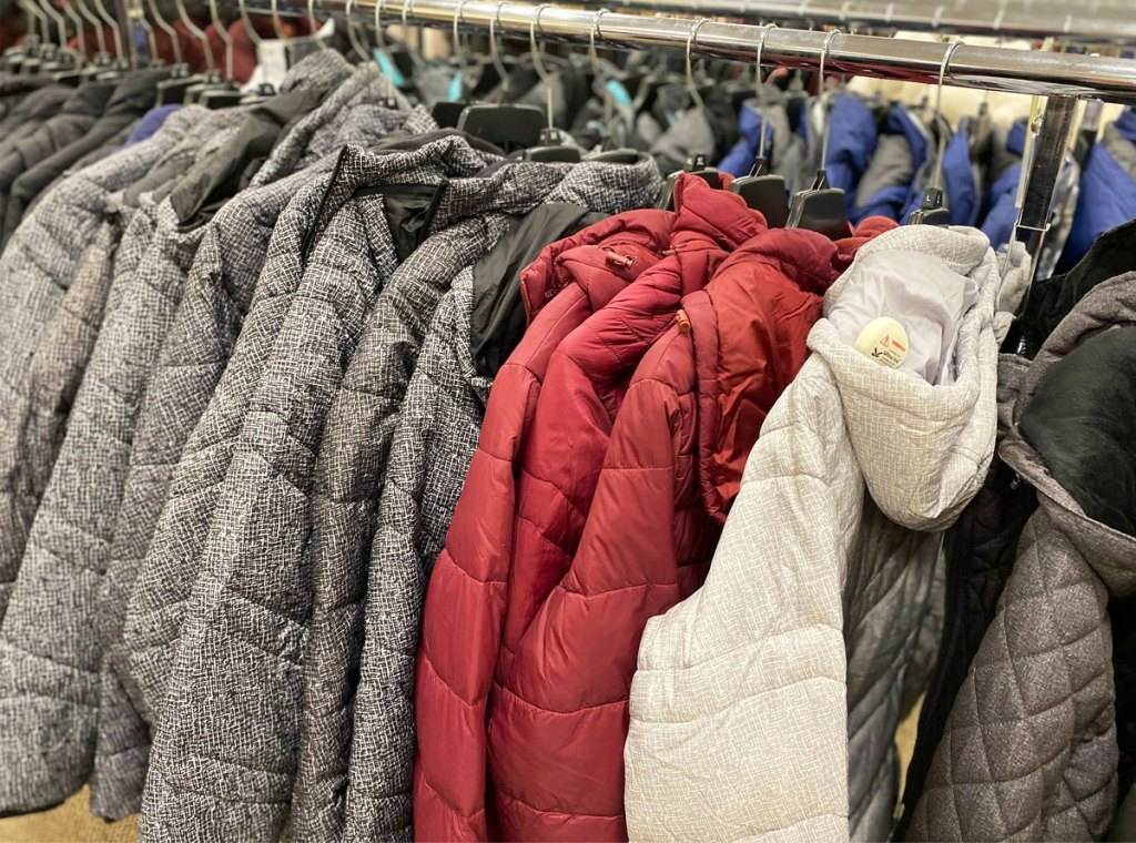rack of kids puffer jackets in grey, maroon, and cream colors
