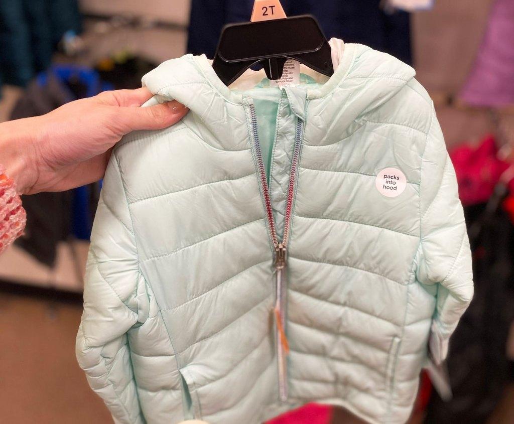 woman holding up a light blue toddler's puffer jacket on a black hanger