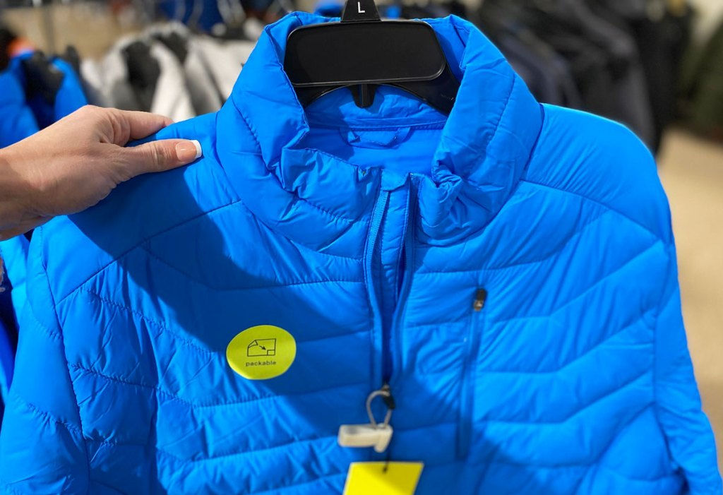 woman holding up a blue puffer jacket on a black hanger