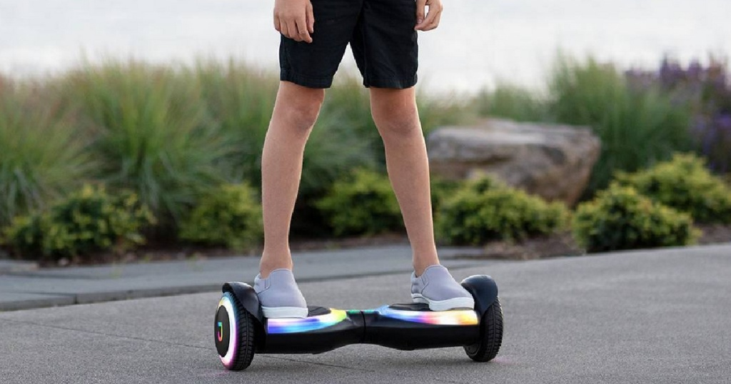 kids standing on black hoverboard with light up wheels outside