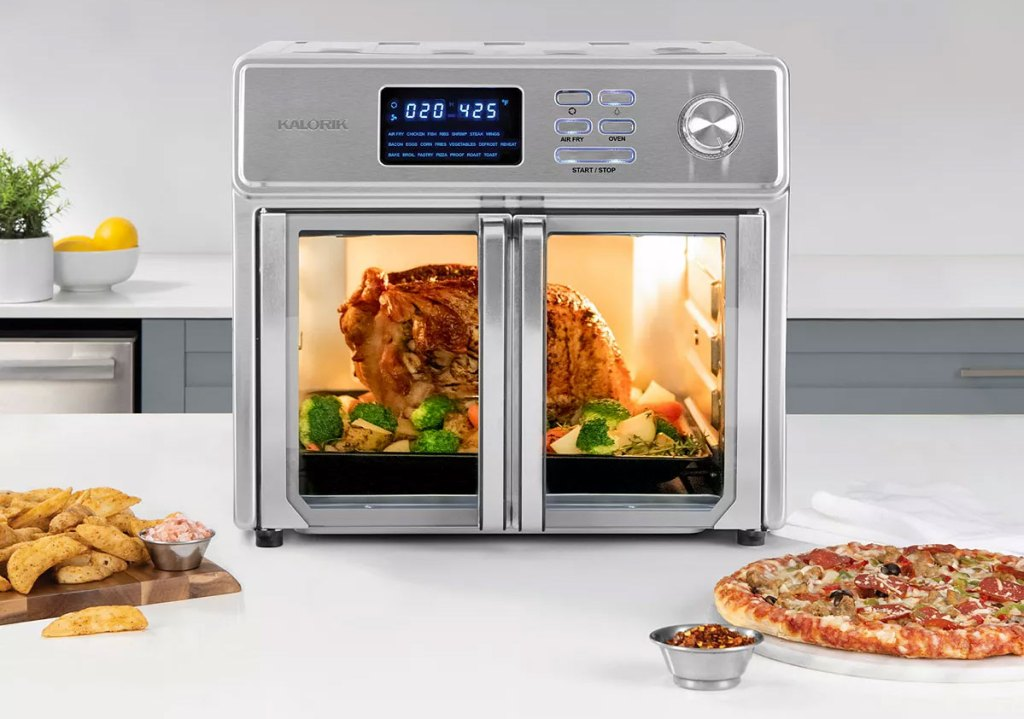 stainless steel air fryer oven on kitchen counter with roast chicken inside and pizza and fries on plates in front of it