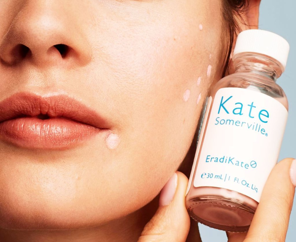 woman holding a bottle of Kate Somerville acne treatment up next to her face with a few spots covered in treatment