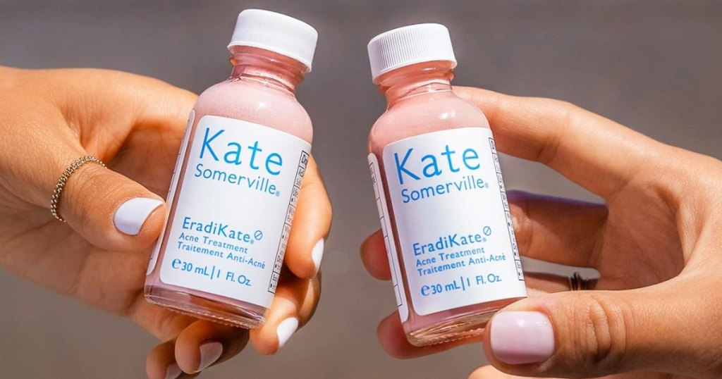 two women with light pink nails holding up two bottles of Kate Somerville acne treatment up next to each other