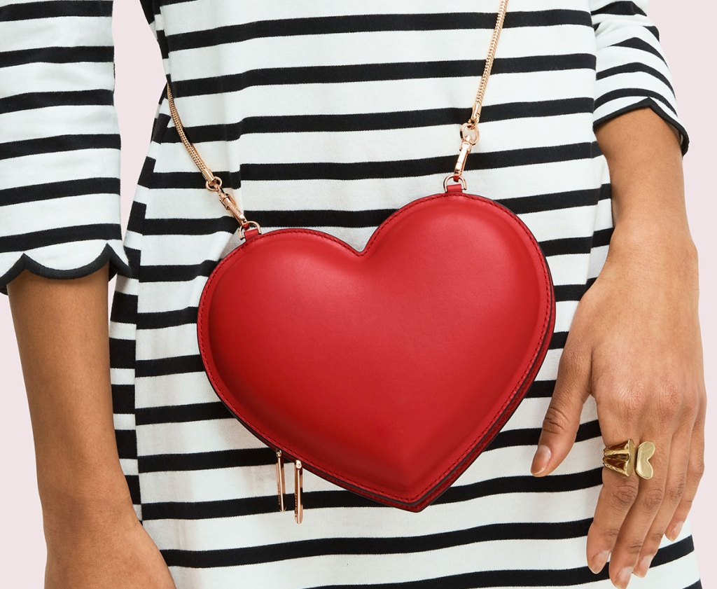 woman in black and white striped dress wearing a red heart shaped crossbody with gold chain strap
